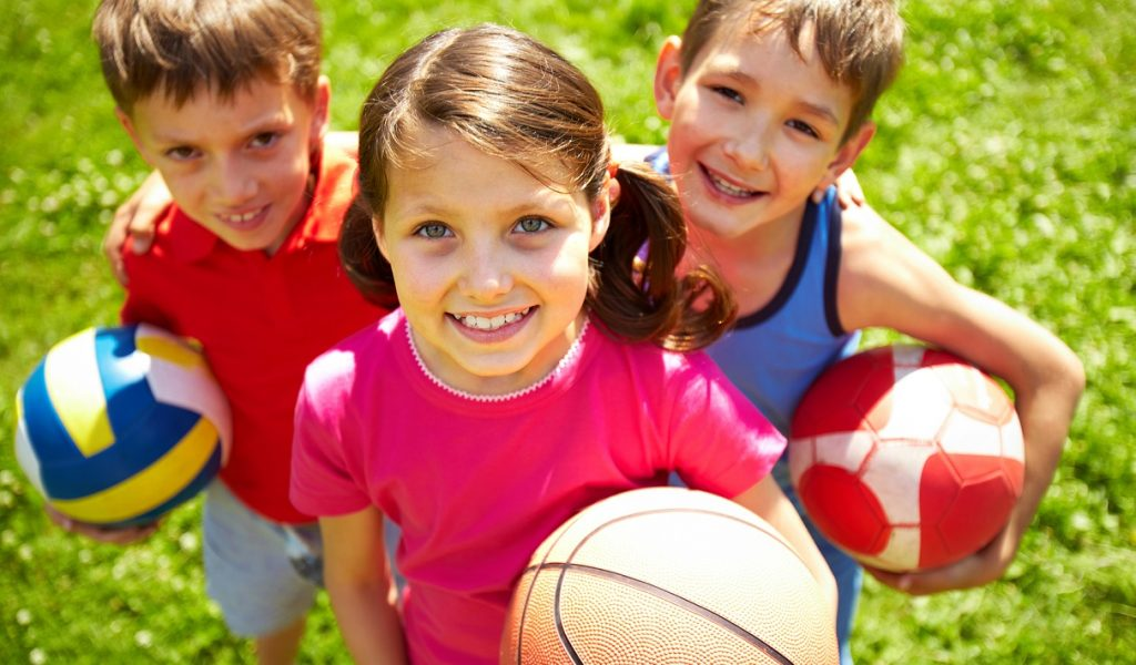 Portrait of three little children with balls looking at camera and smiling